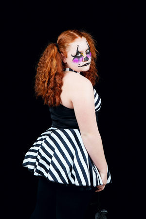 A sad little red-headed clown.  Shot on black background.