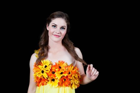 Beautiful woman dressed in a sunshine yellow dress with a yellow and orange daisy bodice.  Shot on black background. Imagens