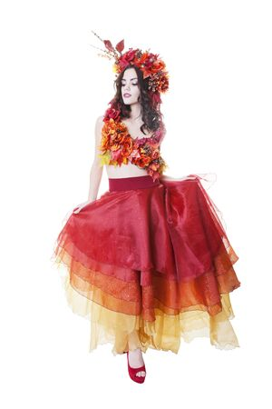 headpiece: A full-length shot of a model dressed in a multi-tiered skirt, with top and headpiece of Autumn leaves and flowers.  Shot on white background.