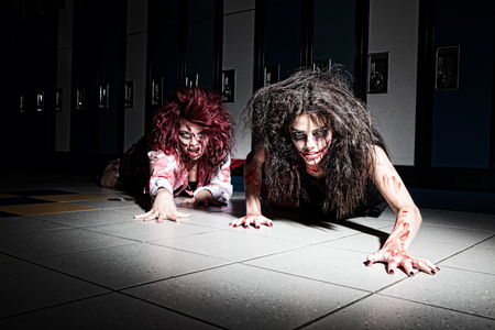 malevolent: Bloody zombie school kids crawling towards the viewer. Stock Photo