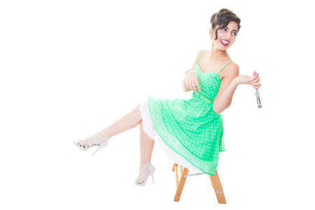 Laughing pinup girl sitting on a small step ladder and holding a hammer.  Shot on white background.