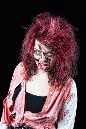cannibal: Snarling, red-headed zombie girl in bloody, tattered clothing.  Shot on black background.
