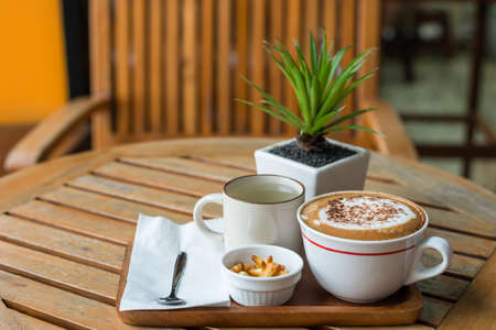 capuchino: Hot capuchino Coffee in white cup on wooden table Stock Photo