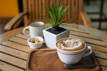 hot chocolate: capuchino caliente de café en la taza blanca en la mesa de madera