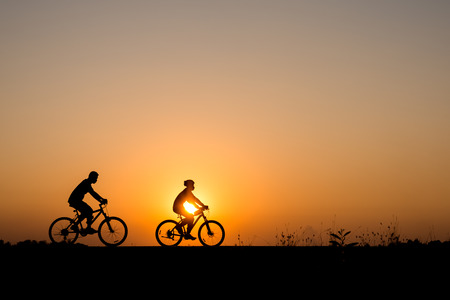bicycle silhouette: Silhouette of cyclist with friend in motion on the background of beautiful sunset