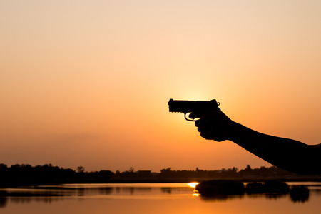 Silhoutte of a man with a handgun at sunset Stock Photo