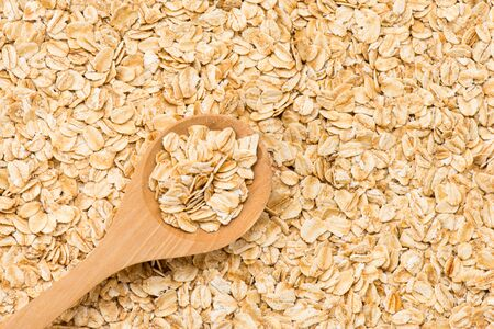 rolled oats: Rolled oats (oat flakes) in a wooden spoon on a rolled oats background. Close-up.