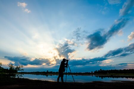Silhouette of a photographer shooting sunset scene
