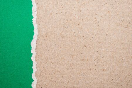 teared paper: Teared, ripped green paper on brown background