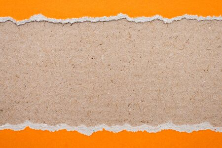 teared paper: Teared, ripped orange paper on brown background