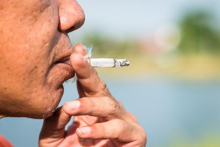 persona fumando: Primer plano de una persona que fuma un cigarrillo