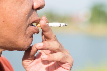 person smoking: Primer plano de una persona que fuma un cigarrillo