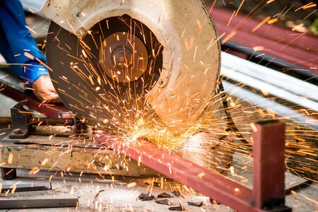 metal cutting saw slicing through a steel pipe. Sparks while grinding iron