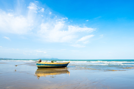Long tail boat on the beach in tropical sea with blue shade sky background