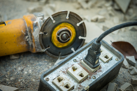 Old power outlet and circular saw put on concrete floor at construction site