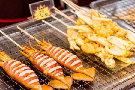 immediate: Grilled squid cooking, Thai food on street food prepared or cooked food sold by vendors in a street or other public location for immediate consumption