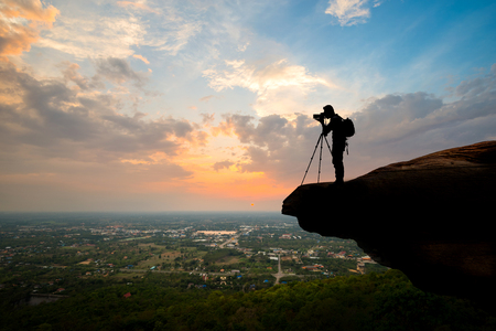 Aerial view Silhouette photographer on top of mountain in sunset background Фото со стока