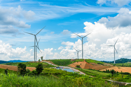 Wind turbine power generators standing on mountain against a blue sky with clouds in a green Paddy field, Located Khao Kho Phetchabun Province, Thailand