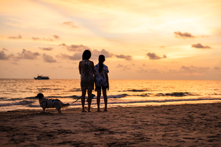Silhouette of Asian girl with dog on the beach on sunset background