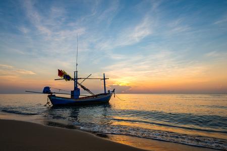 Bunter Himmel bei Sonnenaufgang am Meeresstrand mit Fischerboot. Silhouette Standard-Bild