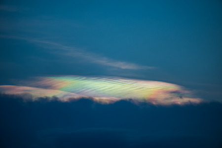 Beautiful abstract iridescence cloud irisation or rainbow cloud shining out from behind the cloud on sunset time