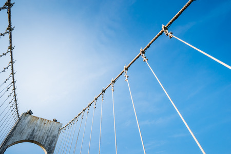 The wire metal rope bridge on blue sky background