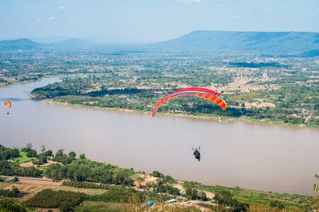 Person practicing paragliding flying sport over the Mekong River, outdoor adventure