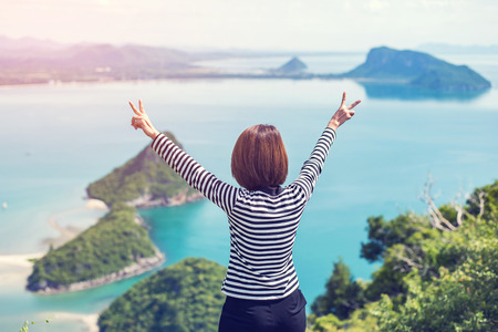 Hipster woman raise up two fingers on the mountain