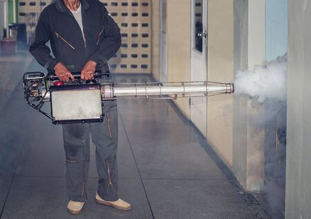 The man's fogging to eliminate mosquito for preventing spread dengue fever and prevent other diseases that have mosquitoes causing the disease