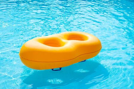 Yellow rubber ring floating in the pool