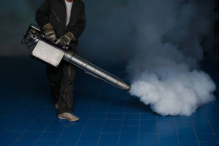 Man work fogging to eliminate mosquito for preventing spread dengue fever in the community 版權商用圖片
