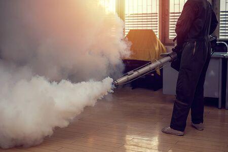 Człowiek pracuje zamgławianie, aby wyeliminować komary, aby zapobiec rozprzestrzenianiu się gorączki denga i wirusa zika