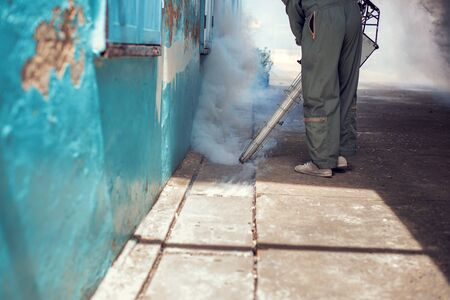 Man work fogging to eliminate mosquito for preventing spread dengue fever in the community Фото со стока