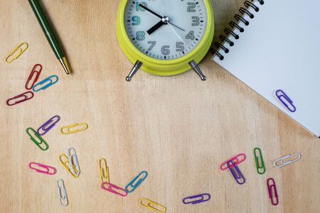 Notebook, pencil, clip, clock on wooden table Imagens