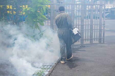 Man work fogging to eliminate mosquito for preventing spread dengue fever