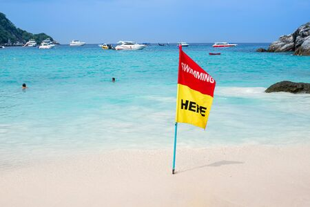 Red and yellow flag show notification for swimming in the sea