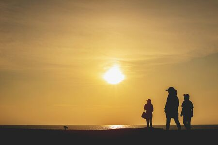 silhouette of people standing and walking on the beach with sunset background 版權商用圖片