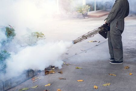 Man work fogging to eliminate mosquito for preventing spread dengue fever