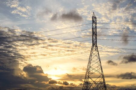High voltage power transmission pole and sunset background