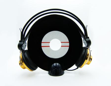 Vinyl single record with golden headphones on white background