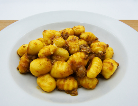 Homemade potato gnocchi with Bolognese sauce (ragu) on a white plate