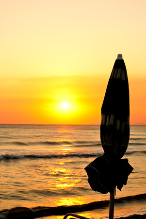 summer is ending, sunset at beach, silhouettes of a beach umbrella with background of an orange sunset over the sea, vertical Stock Photo