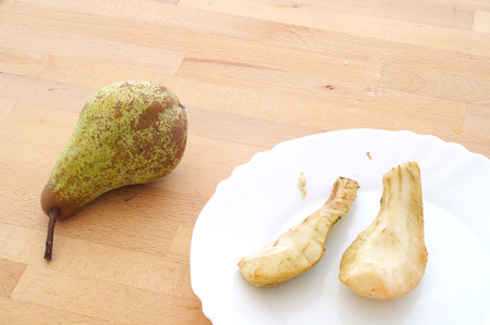 forgotten snack, two pear slices peeled and left to rot on the kitchen table, near a ripe pear