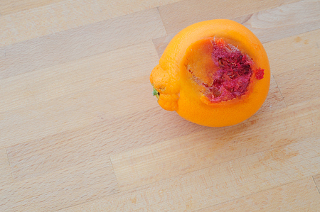 rotten orange on wooden kitchen table, from above