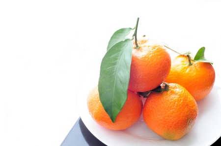 stacks of organic tangerines with green leaves Stock Photo
