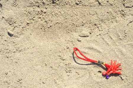 red bracelet lucky charm lost on the beach Stock Photo