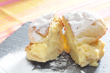 Saint Johns cream puffs, backlighting on a bigne filled with cream cut in two, close up