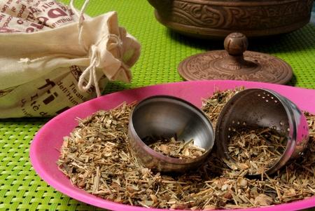 tea filter: A teapot, unfiltered Chinese tea, a tea filter, on a green place mat