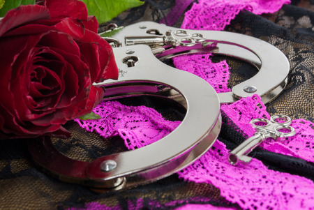 a pair of handcuffs with a red rose for the lady