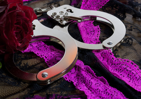a pair of handcuffs with a red rose for the lady photo